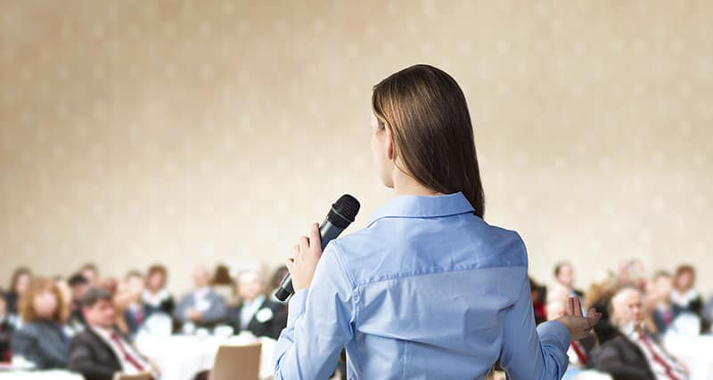 graphicstock-beautiful-business-woman-is-speaking-on-conference_HR-L_1sbb